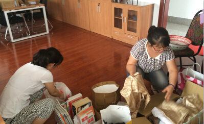 妇委会同志在对捐赠物品进行整理装箱